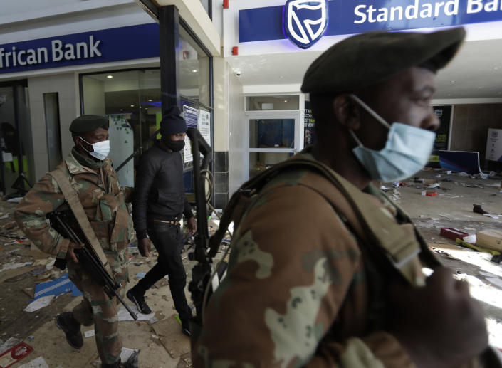 Soldiers escort a man suspected of looting from inside a trashed shopping mall in Soweto, near Johannesburg, Tuesday July 13, 2021. South Africa's rioting continued Tuesday as police and the military tried to halt the unrest in poor areas of two provinces, in Gauteng and KwaZulu-Natal, that began last week after the imprisonment of former President Jacob Zuma. (AP Photo/Themba Hadebe)