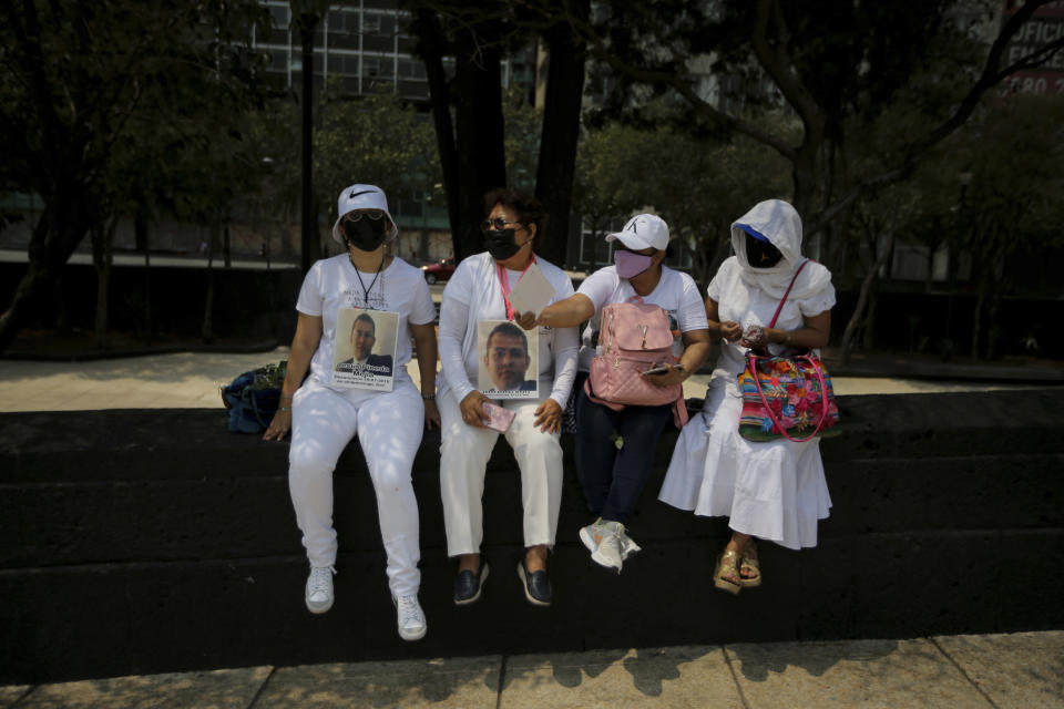 The relatives of disappeared people sit on the sidelines of a march in remembrance of those who have disappeared, on Mother's Day in Mexico City, Monday, May 10, 2021. (AP Photo/Fernando Llano)