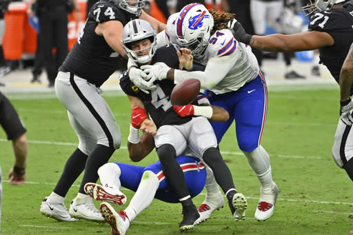 Buffalo Bills defensive tackle Vernon Butler (94) helps take down Las Vegas Raiders quarterback Derek Carr (4) during the second half of an NFL football game, Sunday, Oct. 4, 2020, in Las Vegas. The play was not ruled a fumble. (AP Photo/David Becker)