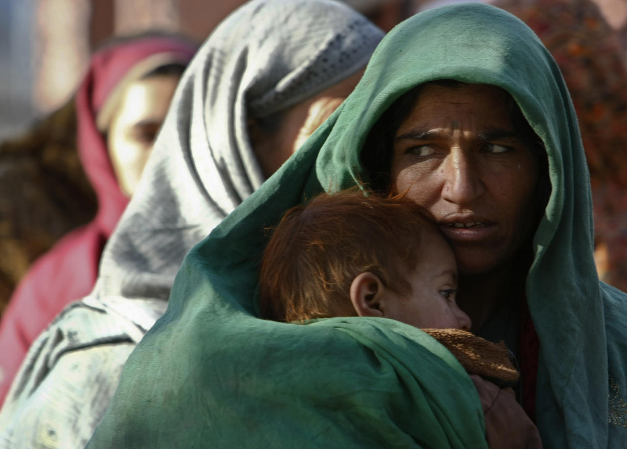 A woman holds her child as she waits in line to receive aid donated by the Turkish government in Kabul March 5, 2012. REUTERS/Omar Sobhani (AFGHANISTAN - Tags: SOCIETY POLITICS)