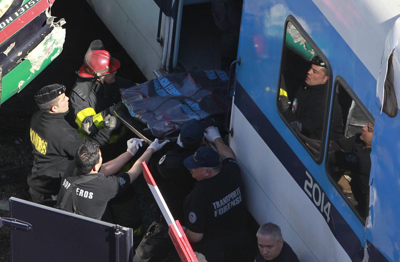 Police retrieve the body of a train crash victim in Buenos Aires, Argentina, Tuesday, Sept. 13, 2011. At least seven people were killed and 162 injured in a rush-hour crash involving two trains and a bus whose driver drove around barriers in an attempt to beat them across the tracks, Argentine authorities said. (AP Photo/Victor R. Caivano)
