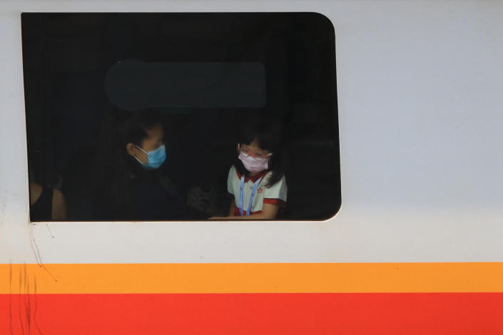 People wearing protective mask look out the window of a commuter train on June 8, 2021 in Singapore. Singapore enters a month long heightened alert from May 16 to June 13 to curb the spread of COVID-19 cases in the local community. New restrictions on movements and activities have been introduced such as limiting social interaction to two, prohibiting dining out and a reduced operating capacity at shopping malls, offices and attractions. (Photo by Suhaimi Abdullah/NurPhoto via Getty Images)