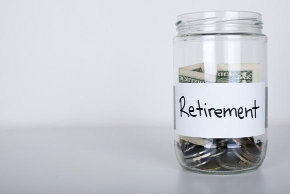 Glass jar of money labeled retirement.