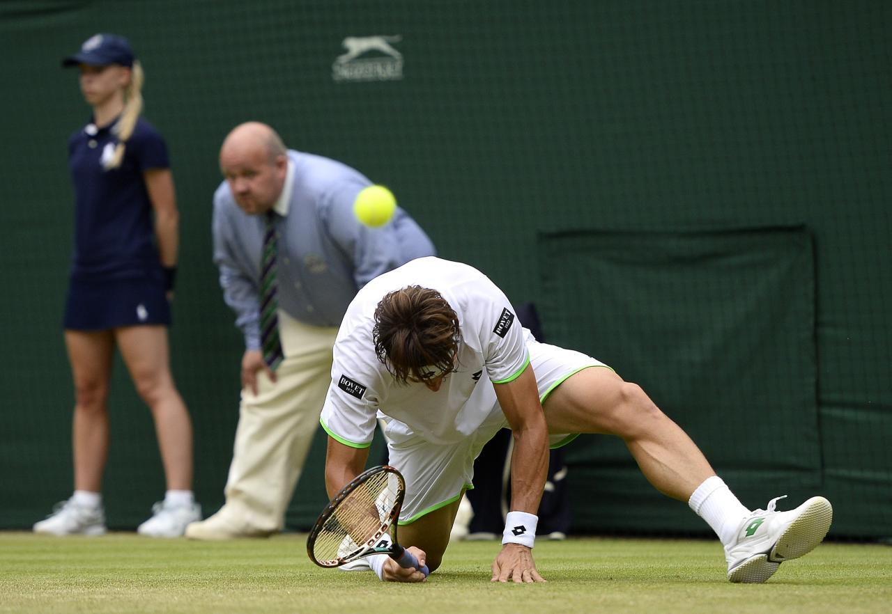 LONDON, ENGLAND - JUNE 28: David Ferrer of Spain gets to his feet after slipping over during his Gentlemen's Singles second round match against Roberto Bautista Agut of Spain on day five of the Wimbledon Lawn Tennis Championships at the All England Lawn Tennis and Croquet Club on June 28, 2013 in London, England. (Photo by Dennis Grombkowski/Getty Images)