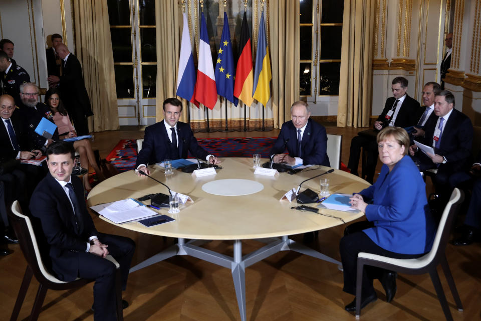 French President Emmanuel Macron, center left, Russian President Vladimir Putin, center right, German Chancellor Angela Merkel and Ukrainian President Volodymyr Zelenskiy, left, attend a working session at the Elysee Palace Monday, Dec. 9, 2019 in Paris. Russian President Vladimir Putin and Ukraine's president are meeting for the first time at a summit in Paris to find a way to end the five years of fighting in eastern Ukraine. (AP Photo/Thibault Camus, Pool)