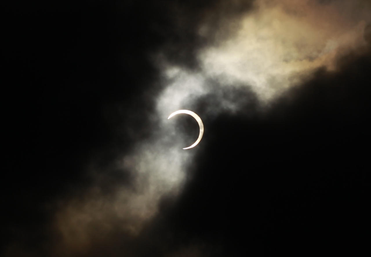 An annular solar eclipse appears during a break in clouds over Taipei, Taiwan, Monday, May 21, 2012. The annular eclipse, in which the moon passes in front of the sun leaving only a golden ring around its edges, was visible to wide areas across China, Japan and elsewhere in the region before moving across the Pacific to be seen in parts of the western United States. (AP Photo/Wally Santana)