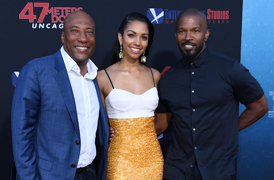 """CEO of Entertainment Studios Byron Allen (L), US actress and model Corinne Foxx (C) and her father US actor Jamie Foxx attend the premiere of """"47 Meteres Down: Uncaged"""" at the Regency Village Theatre in Westwood, California on August 13, 2019. (Photo by VALERIE MACON / AFP)        (Photo credit should read VALERIE MACON/AFP/Getty Images)"""