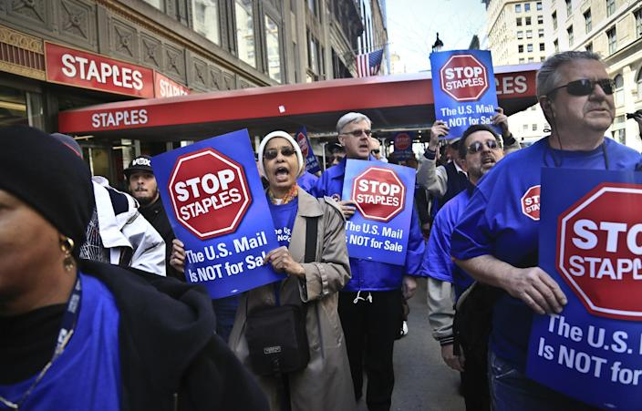 """Post office workers march outside a Staples store chanting """"Stop Staples, the U.S. mail is not for sale,"""" Thursday April 24, 2014 in New York. Thousands of postal workers around the nation are expected to picket outside Staples' stores to protest a pilot program of postal counters in the stores that are staffed with Staples employees. (AP Photo/Bebeto Matthews)"""
