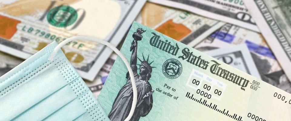 United States Treasury check with US currency and medical or surgical covid mask. Coronavirus economic impact stimulus payments or IRS tax refund.