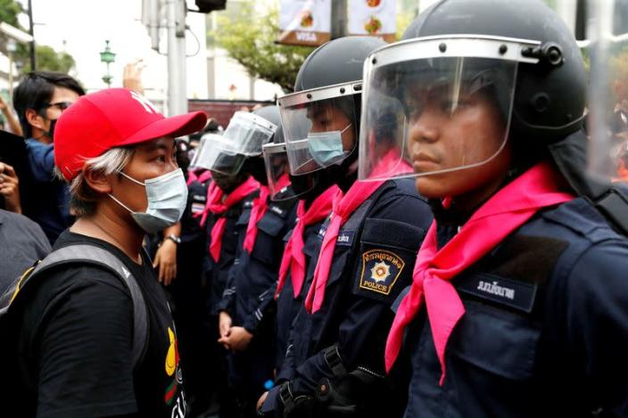FILE PHOTO: A pro-democracy protester stands in front of police officers during anti-government protests in Bangkok