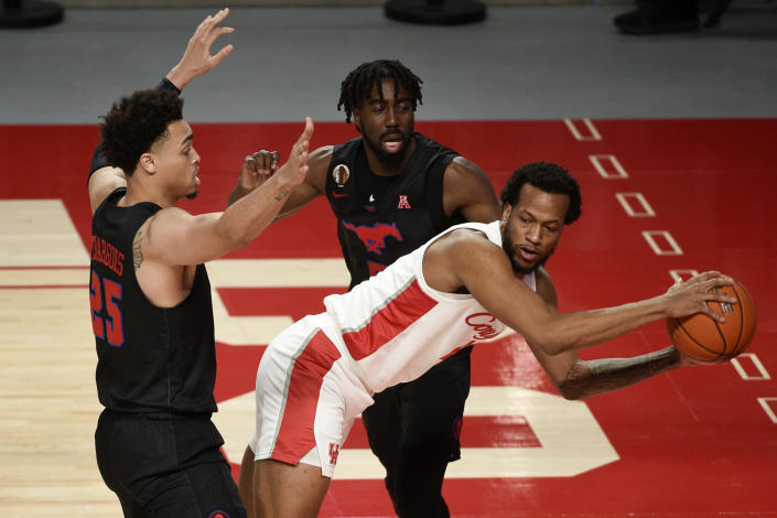 Houston forward Justin Gorham, right, looks to pass as SMU forward Ethan Chargois, left, and Emmanuel Bandoumel, back, defends during the first half of an NCAA college basketball game, Sunday, Jan. 31, 2021, in Houston. (AP Photo/Eric Christian Smith)