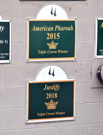 Signs hang at the entrance to barn 33, the Churchill Downs home base for Bob Baffert and his two Triple Crown winners Justify and American Pharoah, Monday, June 11, 2018, in Louisville, Ky. Justify returned to the Kentucky racetrack following his victory in the Belmont Stakes Saturday. (AP Photo/Timothy D. Easley)