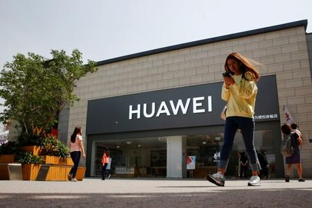 FILE PHOTO: A woman looks at her phone as she walks past a Huawei shop in Beijing
