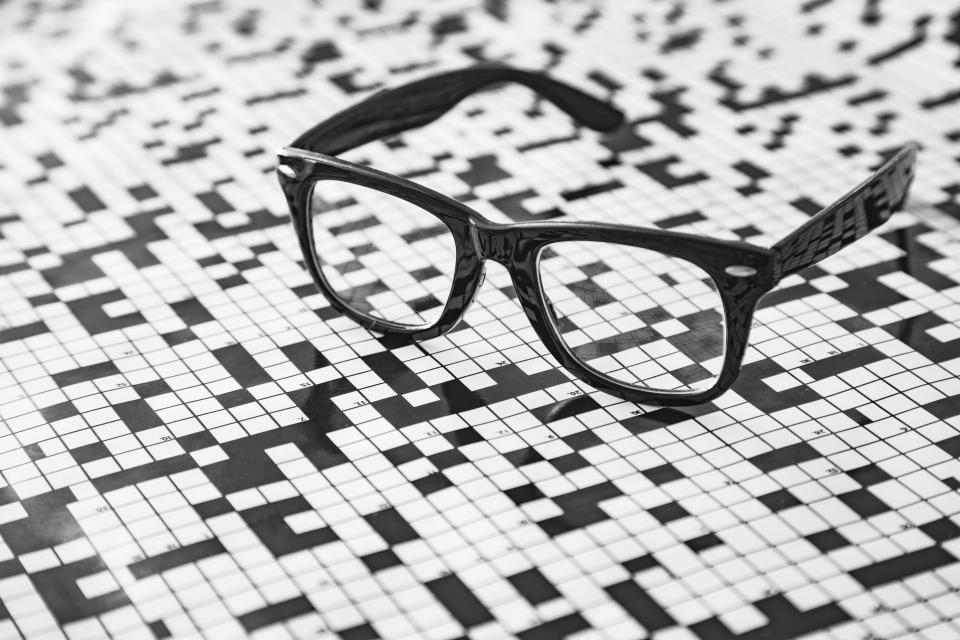 A pair of spectacles with a crossword puzzle background.