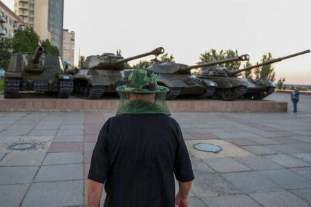 A man wears a mosquito head net as he walks past World War II era tanks in the banks of Volga river in Volgograd, Russia, June 21, 2018. REUTERS/Sergio Perez