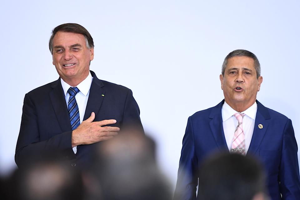 Brazilian President Jair Bolsonaro (L) and his Chief of Staff Braga Netto (R) gesture during the launch of a program to help new mayors at Planalto Palace in Brasilia, on February 23,  2021. (Photo by EVARISTO SA / AFP) (Photo by EVARISTO SA/AFP via Getty Images)