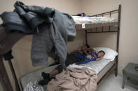 A 4-year-old migrant boy sleeps next to his father at a shelter, Monday, March 22, 2021, in Harlingen, Texas. The father and son were taken into the shelter for the night while they wait for their flight the next morning after they were released from U.S. Customs and Border Protection custody. (AP Photo/Julio Cortez)