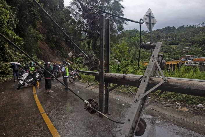 Motorists stop near an electricity pole fell down during an earthquake in Mamuju, West Sulawesi, Indonesia, Saturday, Jan. 16, 2021. Damaged roads and bridges, power blackouts and lack of heavy equipment on Saturday hampered Indonesia's rescuers after a strong and shallow earthquake left a number of people dead and injured on Sulawesi island. (AP Photo/Yusuf Wahil)