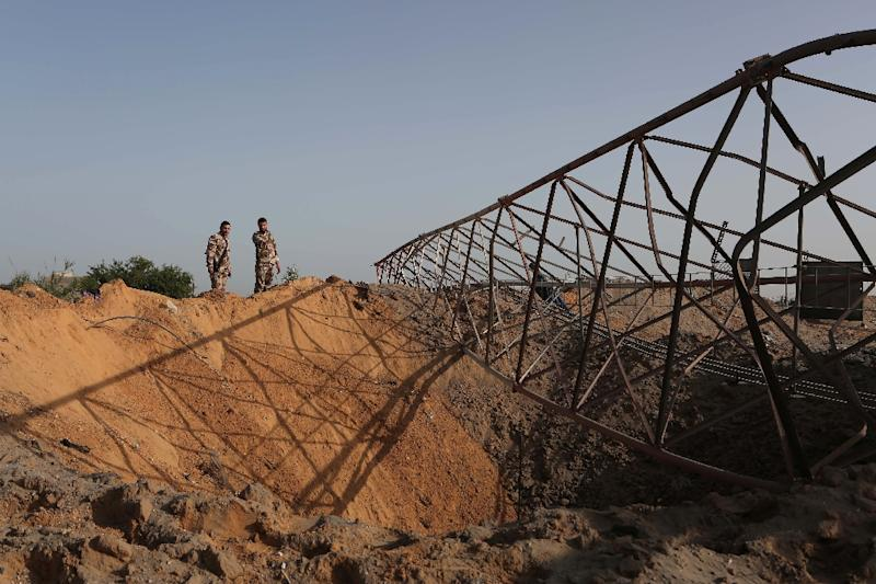 Palestinian security men look at a crater on the ground following an Israeli airstrike in the southern Gaza Strip near the town of Rafah on May 27,2015 (AFP Photo/Said Khatib)