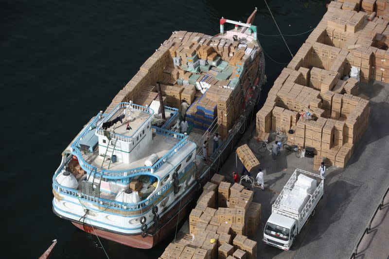 Workers load goods onto a dhow bound for Iran along the creek in old Dubai