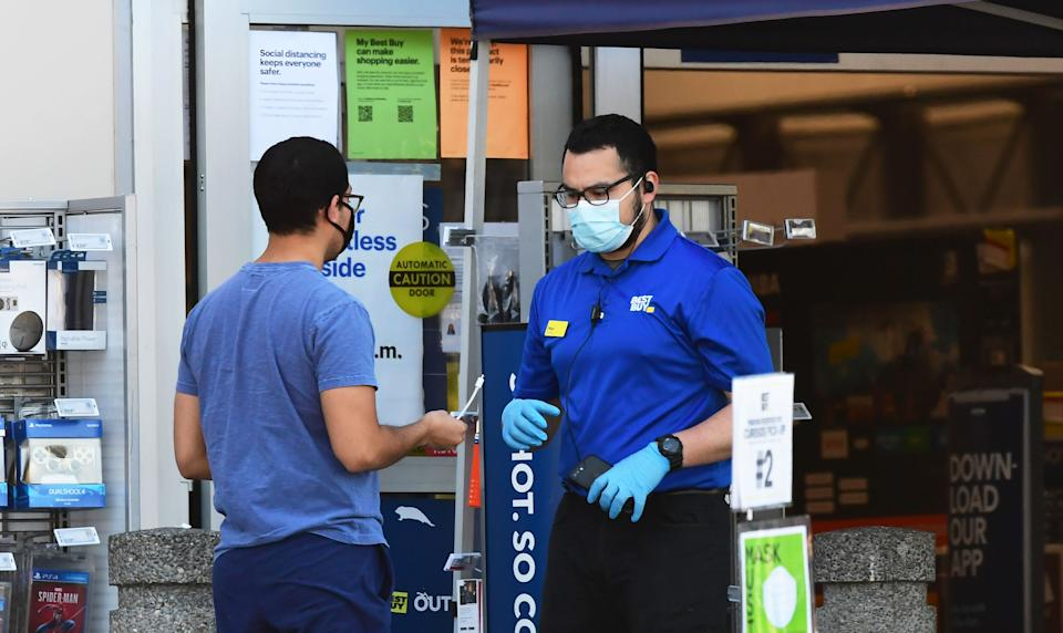 A Best Buy employee tends to a customer outside a store in Montebello, California on April 15, 2020 as the electronics nationwide chain store remains closed to customers but open for pickups. - Best Buy said it will furlough about 51,000 employees as coronavirus-related sales surge ends. (Photo by Frederic J. BROWN / AFP) (Photo by FREDERIC J. BROWN/AFP via Getty Images)