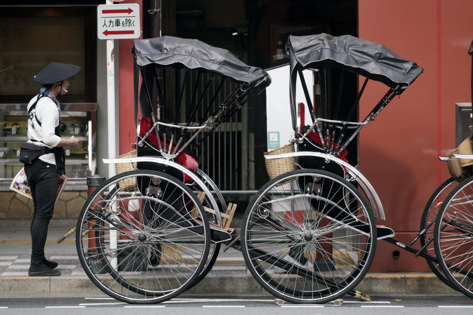 A rickshaw puller waits for tourists near Sensoji Temple in Asakusa district Thursday, Oct. 22, 2020, in Tokyo. (AP Photo/Eugene Hoshiko)
