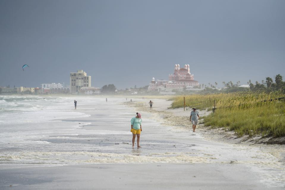 Beach walkers walk along the sand on Pass-a-Grille the morning after Tropical Storm Elsa moved over the Tampa Bay Area, Wednesday, July 7, 2021 in St. Pete Beach, Fla. (Martha Asencio-Rhine/Tampa Bay Times via AP)