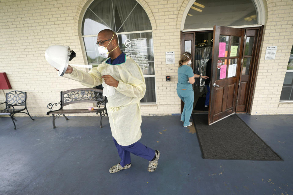 Dr. Robin Armstrong puts on his face shield while demonstrating his full personal protective equipment outside the entrance to The Resort at Texas City nursing home, where he is the medical director, Tuesday, April 7, 2020, in Texas City, Texas. Armstrong is treating nearly 30 residents of the nursing home with the anti-malaria drug hydroxychloroquine, which is unproven against COVID-19 even as President Donald Trump heavily promotes it as a possible treatment. Armstrong said Trump's championing of the drug is giving doctors more access to try it on coronavirus patients. More than 80 residents and workers have tested positive for coronavirus at the nursing home. (AP Photo/David J. Phillip)