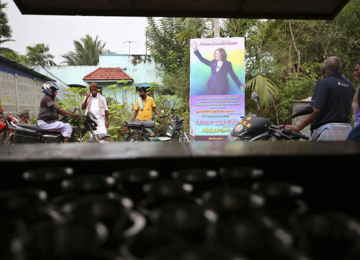 FILE - In this Jan. 20, 2021, file photo, Indian villagers gather outside a local eatery next to a banner featuring Vice President-elect Kamala Harris with a message wishing her best, in Thulasendrapuram, the hometown of Harris' maternal grandfather, south of Chennai, Tamil Nadu state, India. A tiny village in a remote part of South India is gearing up for celebrations ahead of Kamala Harris' inauguration as the first female vice president of the United States. (AP Photo/Aijaz Rahi)