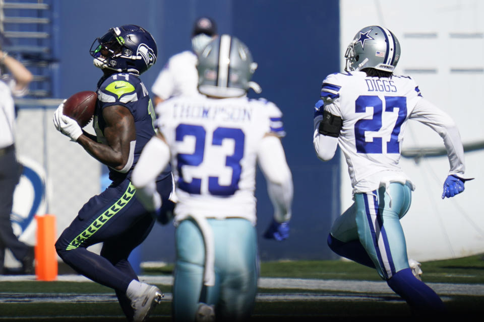 Seattle Seahawks wide receiver DK Metcalf, left, catches a pass from quarterback Russell Wilson near the end zone, but the ball was knocked loose by Dallas Cowboys cornerback Trevon Diggs during the first half of an NFL football game, Sunday, Sept. 27, 2020, in Seattle. (AP Photo/Elaine Thompson)