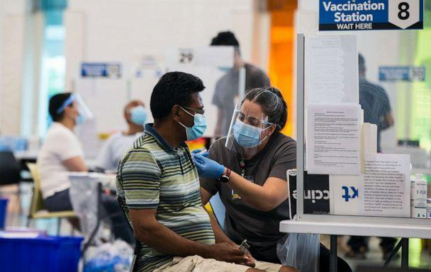 PHOTO: A staff member administers a COVID-19 vaccine to a man at a vaccination clinic at Save Max Sports Center in Brampton, Ontario, Canada, on July 10, 2021 (Zou Zheng/Xinhua via Newscom)
