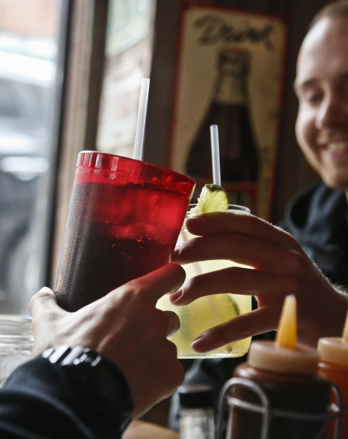 FILE - In this March 8, 2013 file photo, customers at Brother Jimmy's BBQ call cheers with 24-ounce, left, and 16-ounce beverages, in New York. New York City's groundbreaking limit on the size of sugar-laden drinks has been struck down by a judge shortly before it was set to take effect. The restriction was supposed to start Tuesday, March 12, 2013. The rule prohibits selling non-diet soda and some other sugary beverages in containers bigger than 16 ounces. It applies at places ranging from pizzerias to sports stadiums, though not at supermarkets or convenience stores. (AP Photo/Bebeto Matthews)