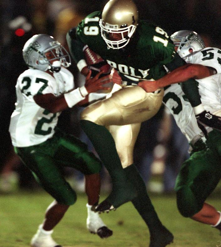 Long Beach Poly's Marcedes Lewis tries to rush past Concord De La Salle defenders Alijah Bradley and Cole Smith.