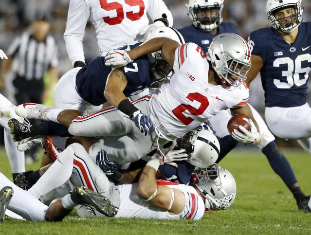 FILE - In this Saturday, Sept. 29, 2018 file photo, Ohio State's J.K. Dobbins (2) is tackled by Penn State's Koa Farmer (7) during the first half of an NCAA college football game in State College, Pa. J.K. Dobbins wants to make up for his failure last season. Despite rushing for over 1,000 yards, Dobbins calls 2018 a disappointment. He had a drop-off from his record-breaking freshman year and is determined to get back to that level and prove hes best running back in the nation.(AP Photo/Chris Knight, File)