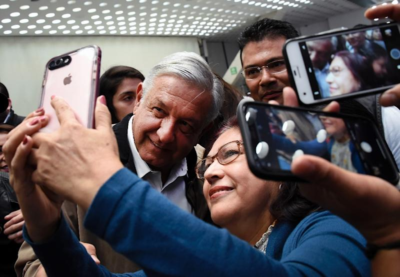 Even aboard a plane, Mexico President Andres Manuel Lopez Obrador takes the time to pose for photos with other passengers, much to the chagrin of flight attendants (AFP Photo/Alfredo ESTRELLA)