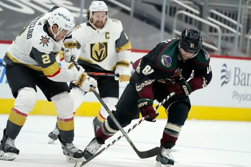 Vegas Golden Knights defenseman Zach Whitecloud (2) bounces the puck off the skate of Arizona Coyotes right wing Phil Kessel (81) as Golden Knights right wing Mark Stone, center, looks on during the third period of an NHL hockey game Friday, Jan. 22, 2021, in Glendale, Ariz. (AP Photo/Ross D. Franklin)