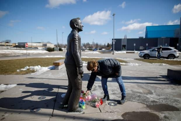 A woman places flowers at the foot of a statue depicting Walter Gretzky outside the Wayne Gretzky Sports Centre in Brantford, Ont., following news of his death.