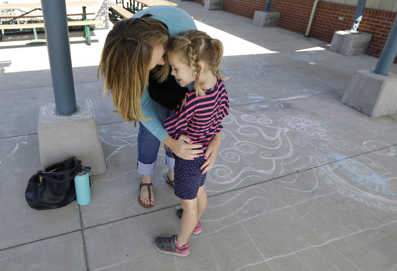 """In this Tuesday, July 11, 2017 photo, Molly Maxwell hugs her child Gracie at the Bay Area Rainbow Day Camp in El Cerrito, Calif. The camp caters to transgender and """"gender fluid"""" children, aged 4-12, making it one of the only camps of its kind in the world open to preschoolers, experts say. (AP Photo/Jeff Chiu)"""