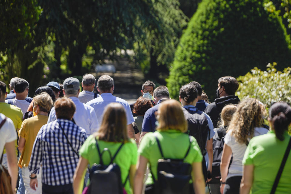 A guide, center, accompanies visitors in the gardens of the Papal Palace in Castel Gandolfo, some 30 kilometers southeast of Rome, Saturday, May 29, 2021. As Covid-19 restrictions are slowly being lifted in Italy, thousands of people are returning to visit the extensive gardens and apartments at the Papal Palace of Castel Gandolfo in the Alban Hills near Rome, that for hundreds of years have been the summer retreat for Popes seeking to escape the suffocating heat of Rome. (AP Photo/Andrew Medichini)