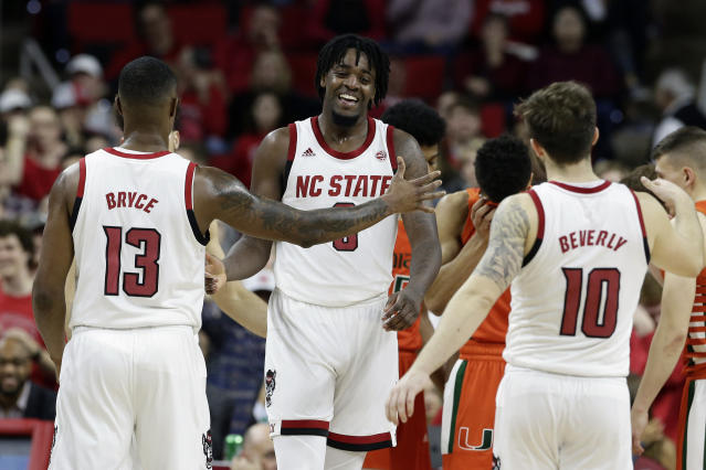 North Carolina State forward D.J. Funderburk, center, is congratulated by guard C.J. Bryce (13) and guard Braxton Beverly (10) during the second half of an NCAA college basketball game against Miami in Raleigh, N.C., Wednesday, Jan. 15, 2020. (AP Photo/Gerry Broome)