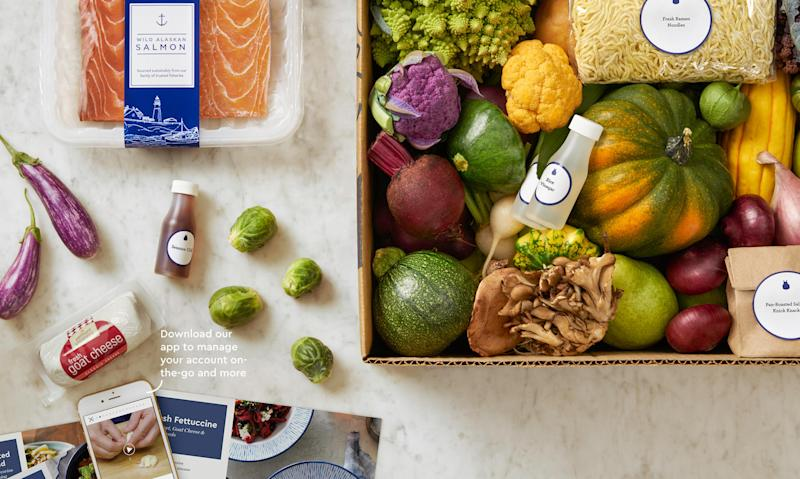 A Blue Apron meal kit, consisting of various ingredients neatly placed in a box and on a table.