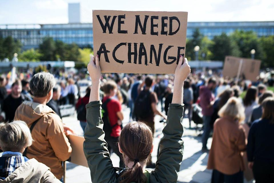Young person photographed from behind holding a sign saying WE NEED A CHANGE
