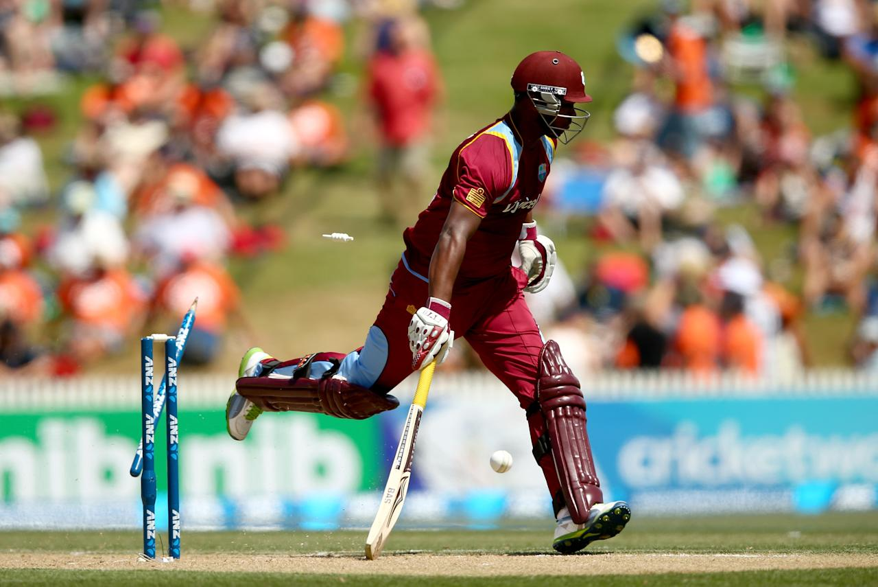 HAMILTON, NEW ZEALAND - JANUARY 08: Johnson Charles of the West Indies is run out by Nathan McCullum of New Zealand during game five of the One Day International Series between New Zealand and the West Indies at Seddon Park on January 8, 2014 in Hamilton, New Zealand.  (Photo by Phil Walter/Getty Images)