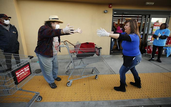 "Michell Guajardo, right, owner and operator of the Grocery Outlet Bargain Market in Altadena, gives a social distancing air hug to Jim Steinberg, 67, as senior shoppers lined up outside before dawn Thursday. <span class=""copyright"">(Al Seib/Los Angeles Times)</span>"