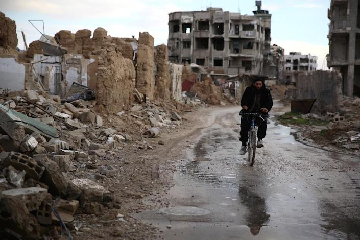 A Syrian man rides a bike in the neighbourhood of Jobar, on the eastern outskirts of the capital Damascus, on January 23, 2016 (AFP Photo/Abd Doumany)