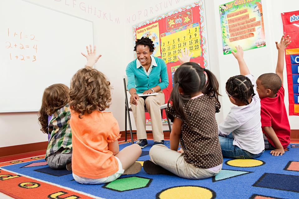 A teacher smiles as her students sit on the rug and raise their hands