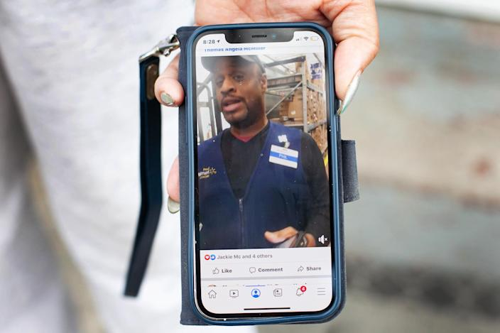 Image: Angela McMiller holds her phone displaying a photo of her late brother Phillip Thomas. (Eddie Quinones / for NBC News)