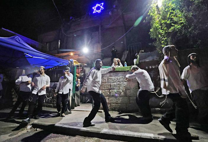 Israeli settlers dance in front of a house decorated with the Star of David in the Sheikh Jarrah neighborhood of Israeli-annexed east Jerusalem on May 9, 2021. (Emmanuel Dunand / AFP - Getty Images)
