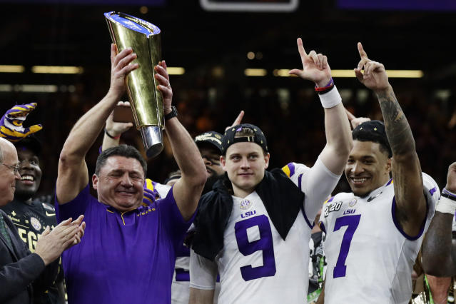 LSU head coach Ed Orgeron holds the trophy beside quarterback Joe Burrow, center, and safety Grant Delpit after a NCAA College Football Playoff national championship game against Clemson, Monday, Jan. 13, 2020, in New Orleans. LSU won 42-25. (AP Photo/Sue Ogrocki)