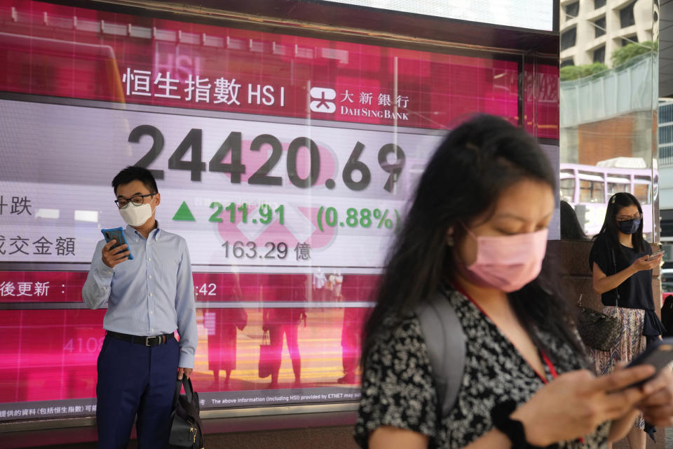 People wearing face masks walk past a bank's electronic board showing the Hong Kong share index in Hong Kong, Tuesday, Sept. 28, 2021. Asian shares mostly fell Tuesday as concerns about China chipped away at investor optimism following a mixed finish on Wall Street. (AP Photo/Kin Cheung)